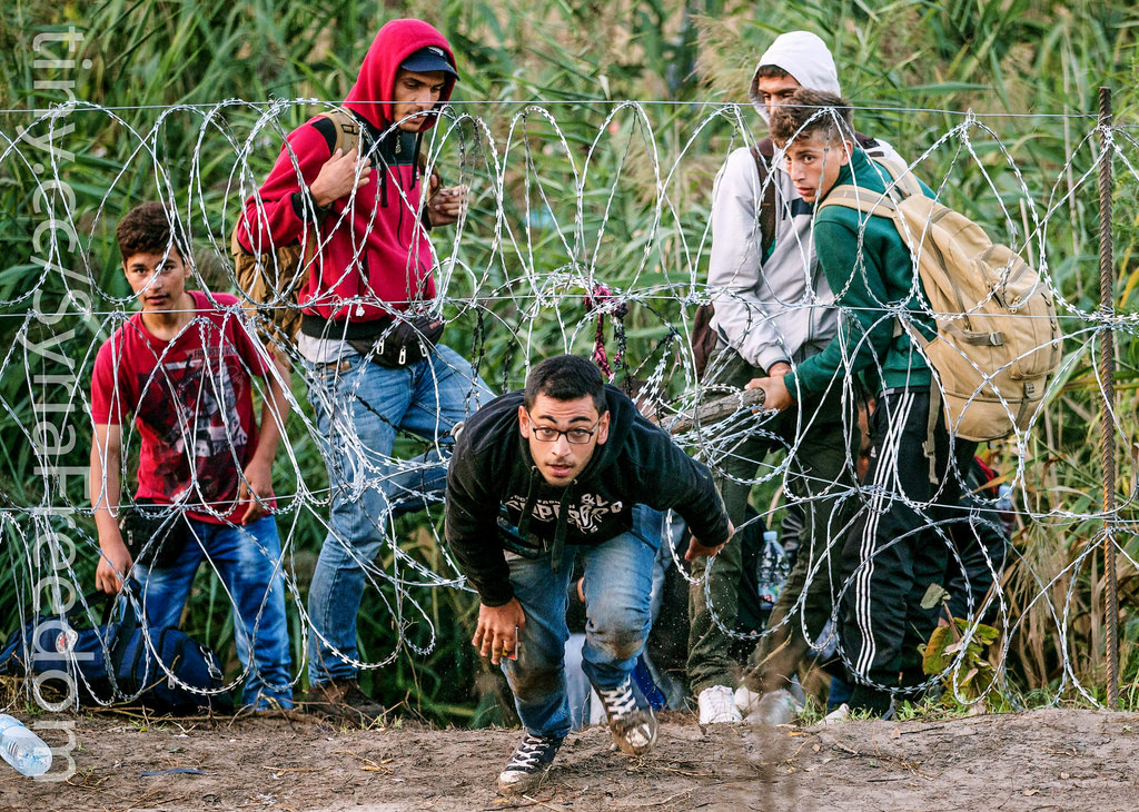Syrian refugees sneaking through a barbed-wire fence