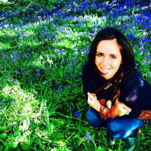 This is a portrait photograph of the author, Karis Jade Petty, sitting in a woodland where the ground is covered with bluebells.