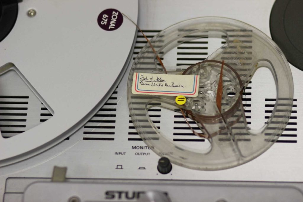 Image of a small open reel tape on a reel to reel tape recorder