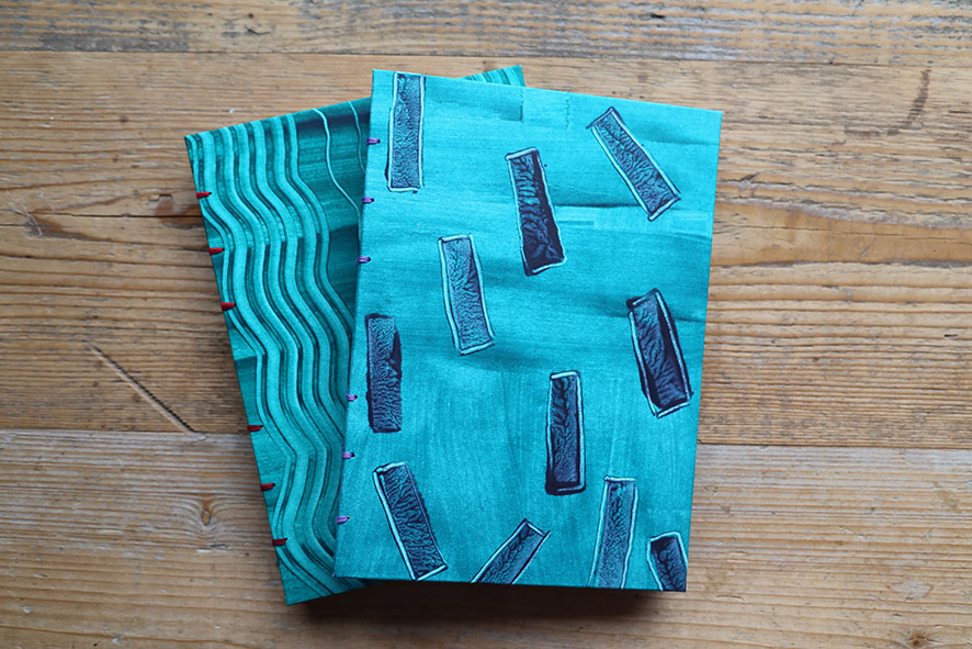 2 turquoise paste patterned covered notebooks