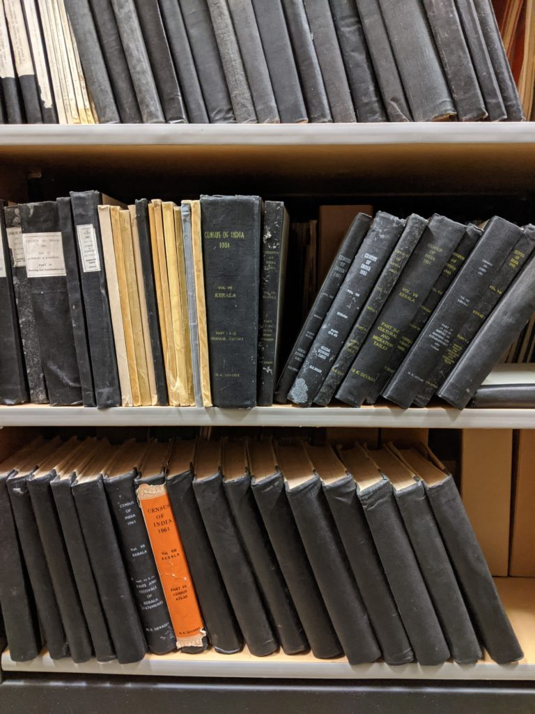 Shelves with large handback books containing Indian census material, some fallen over