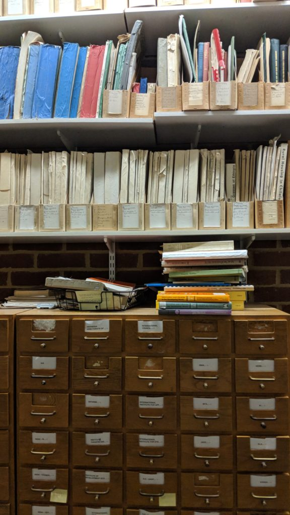 2 shelves on wall containing pamphlets above a card catalogue