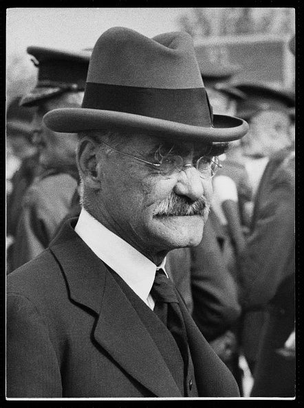 A side portrait of Rudyard Kipling in a crowd of officers wearing a suit and tie and a hat