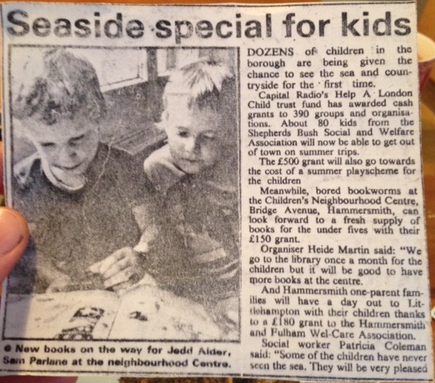 A newspaper clipping titled Seaside Special for Kids including a photo of a young Sam reading a book with another child