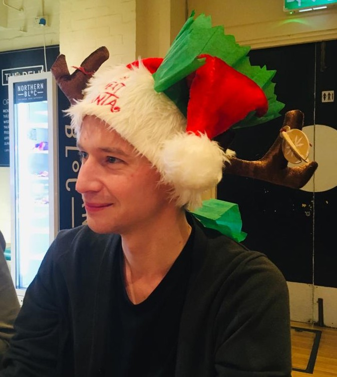 Kane, a man wearing multiple Christmas hats, smiles.