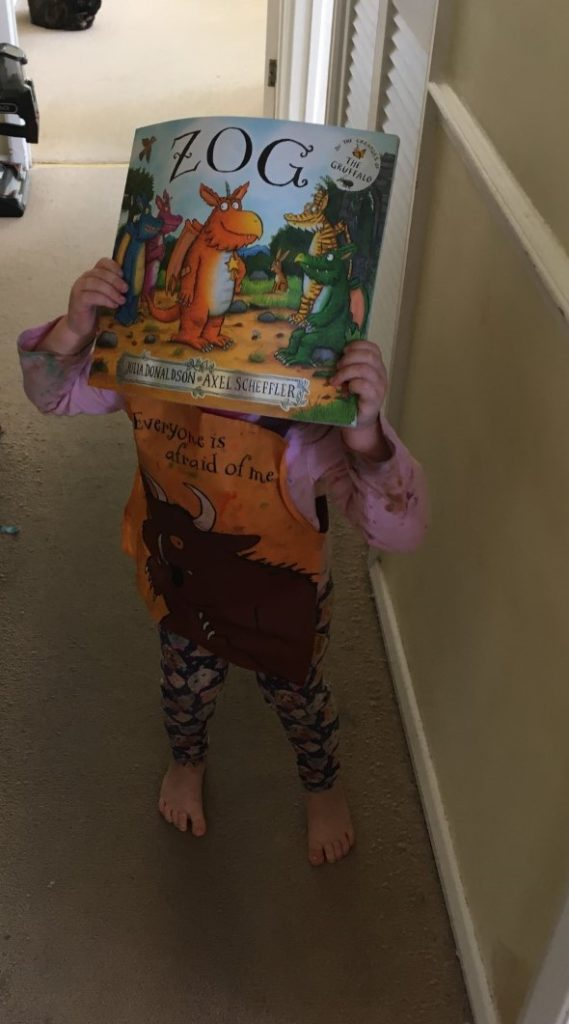 A child holding up a copy of the book Zog.