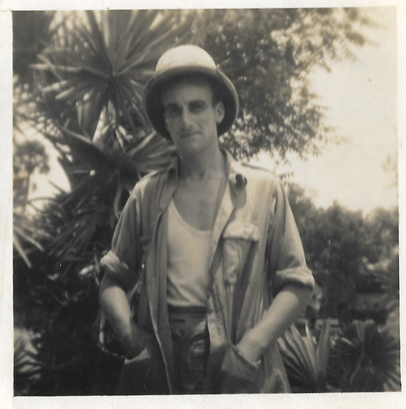 A man wearing 1940s military uniform in the jungle.