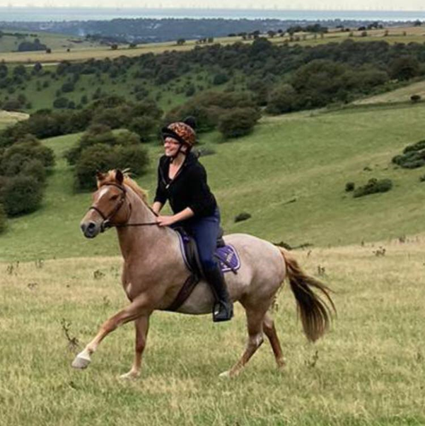 A woman rides a horse across fields. She is smiling.