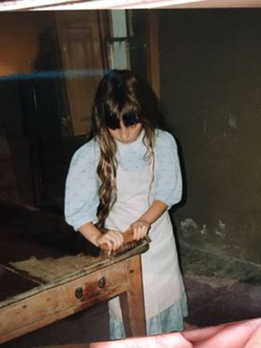 A little girl dressed in Victorian clothes scrubs a table.