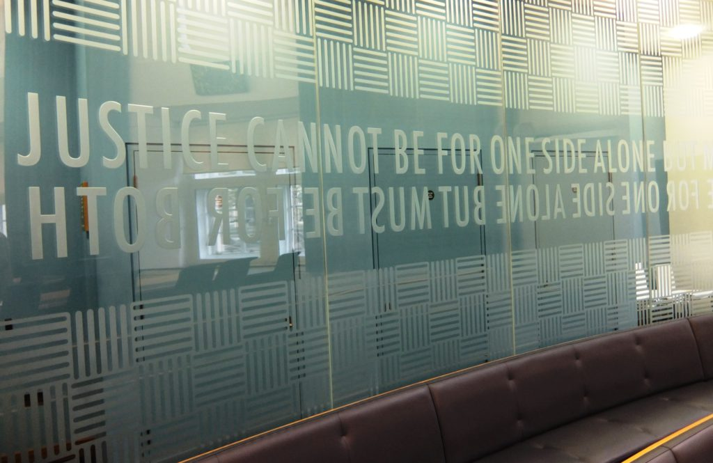 "picture of Court 2 - the glass wall allows visitors to stand behind it or sit in the public benches in front. The screen is etched with the words: ""Justice cannot be for one side alone but must be for both""."