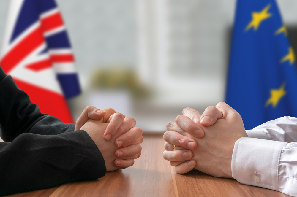 politicians with clasped hands and UK / EU flags